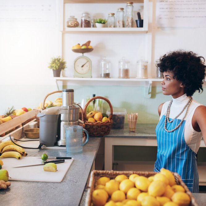 Indoor shot of young female bartender wearing apron standing at juice bar counter looking away and thinking.